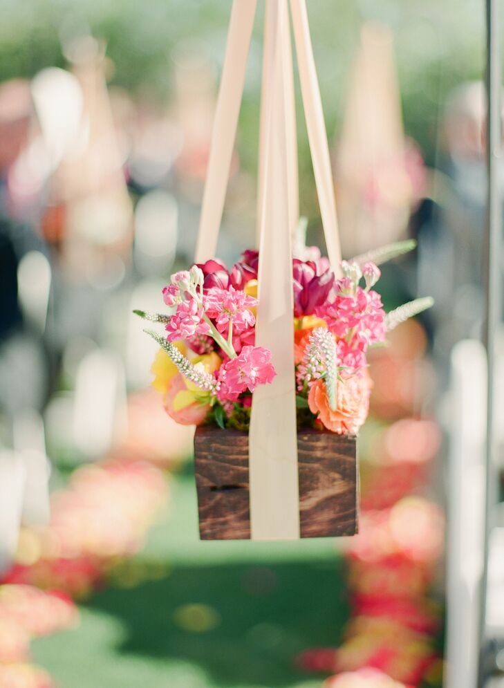"""""""I had very simple ceremony decorations. We had sunset-colored petals (magenta, yellow, orange) along the sides of the aisle. In addition we had shepherd hooks lining the aisle with small wooden boxes filled with green amaranthus, jasmine, yellow and orange ranunculus, plum tulips, assorted succulents and veronica. It was the perfect accessory to an already gorgeous desert backdrop."""""""