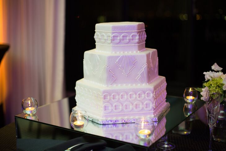 The wedding cake by Susie's Cakes in Houston, Texas, featured three hexagonal white tiers covered in an intricate, detailed pattern to add an art-deco twist to the formal reception.