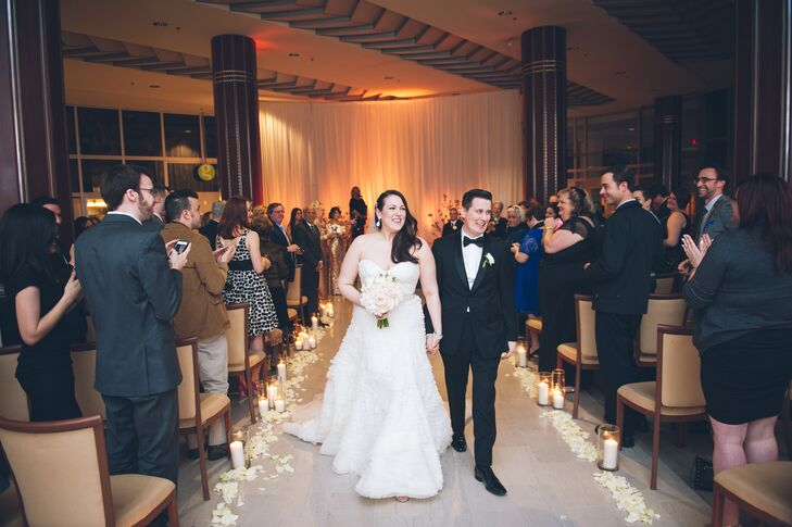 """You are the Best Thing"" by Ray LaMontagne filled the room as Pamela and Dan started their recessional. Fleurescent, their florist, extended the couple's romantic ceremony backdrop with  soft arrangements.Ivory rose petals separated each cylinder vase as soft candelight glowed within it."