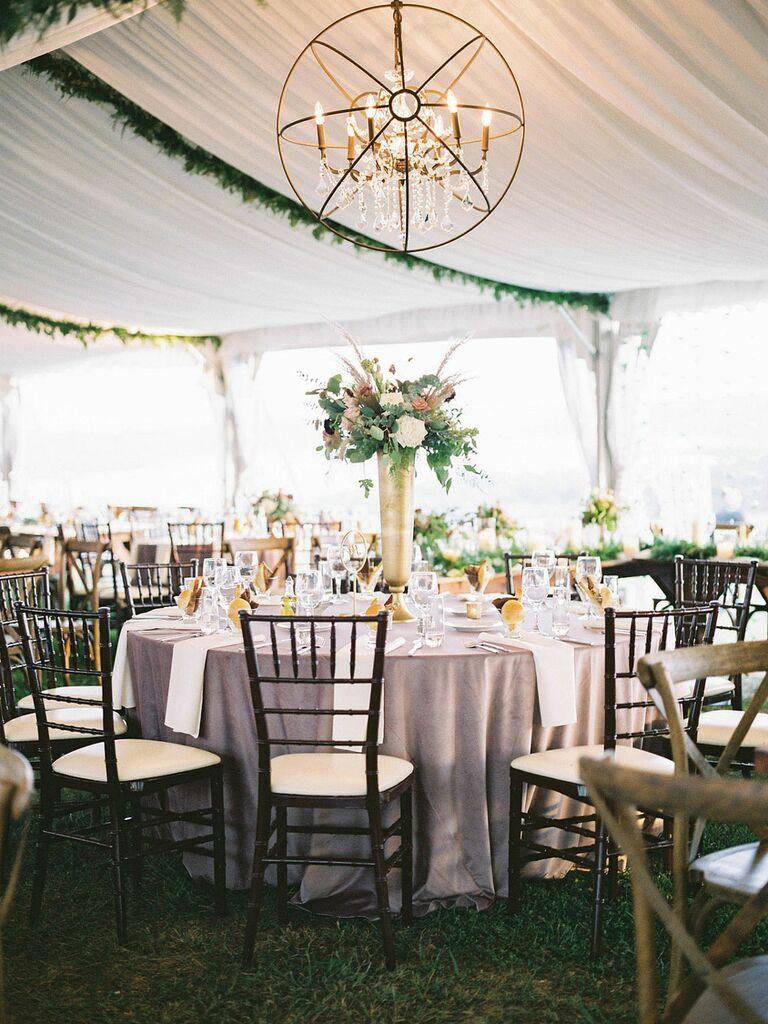 Modern chandelier hanging from outdoor wedding tent
