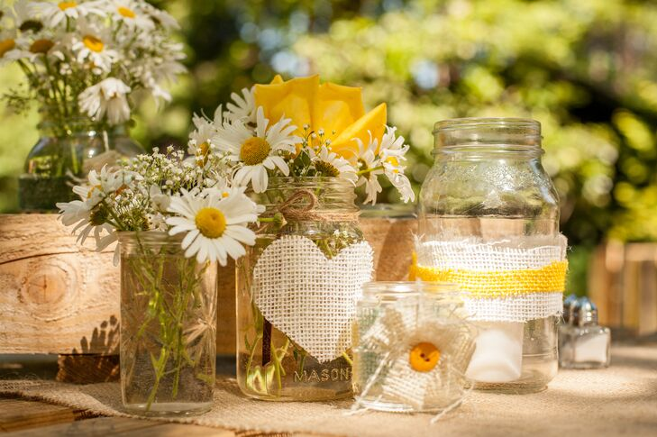 White daisies and yellow roses filled glass mason jars that served as table centerpieces.