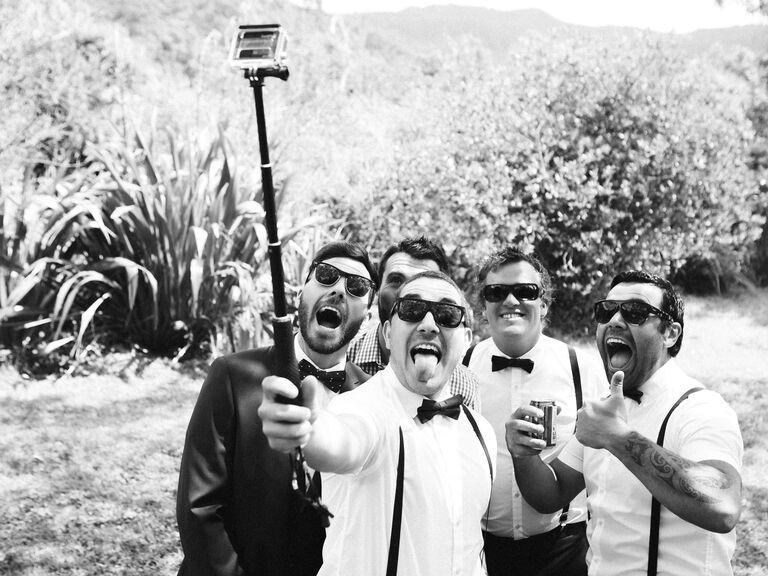 Groomsmen que usam uma vara do selfie em um casamento.