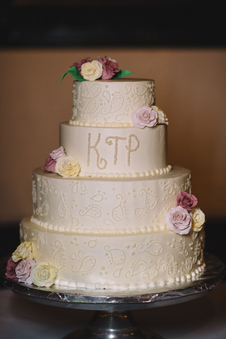 After dinner, Kara and Pat enjoyed a four-tier cake made by the venue. It was decorated with a subtle paisley design and their monogram in the middle. Ivory, lavender and burgundy sugar roses added a little romance to the cake.