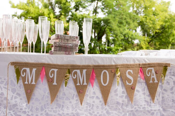 After the early-morning ceremony, guests enjoyed mimosas during cocktail hour. Terri and Jerome love waking up on the weekends and eating breakfast together, so served brunch for their wedding. The cocktail table was decorated with burlap bunting to match the rustic theme.