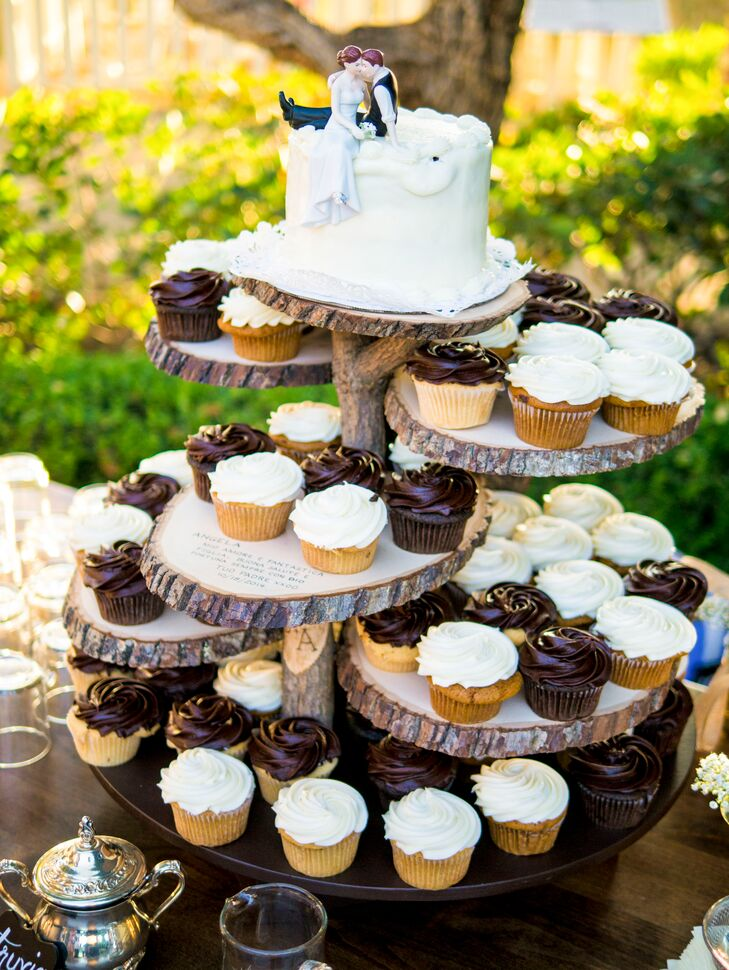"The single tiered ivory wedding cake had a bride and groom cake topper, which sat above an arrangement of cupcakes. ""For dessert, we had cake and cupcakes that were displayed on my dad's gorgeous cake stand and guests also had coffee and tea options. The cupcake flavors were chocolate with chocolate icing, vanilla with chocolate icing, banana with cream cheese icing, and pumpkin with cream cheese icing."""