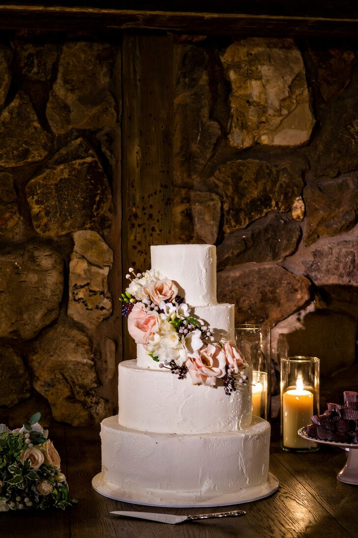 A cascade of blush roses and white tuberoses decorated the simple four-tier buttercream cake.