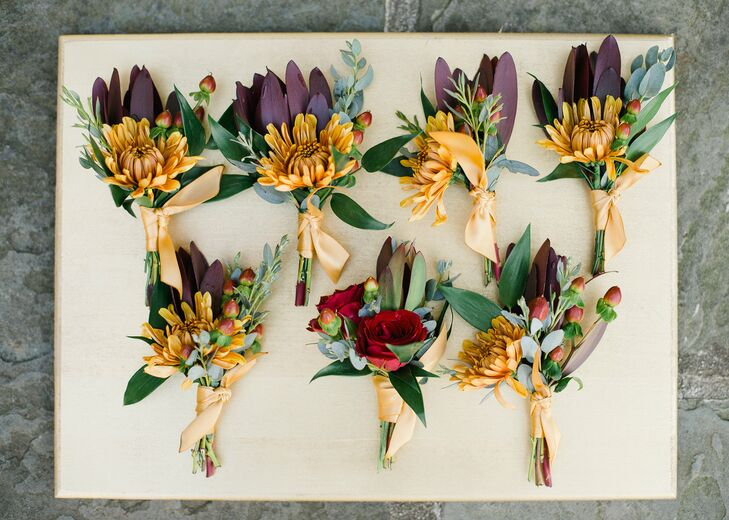 Drawing on the colors of the season, the boutonnieres were filled with mums, roses, hypericum berries and greenery in shades of deep burgundy, gold and red.