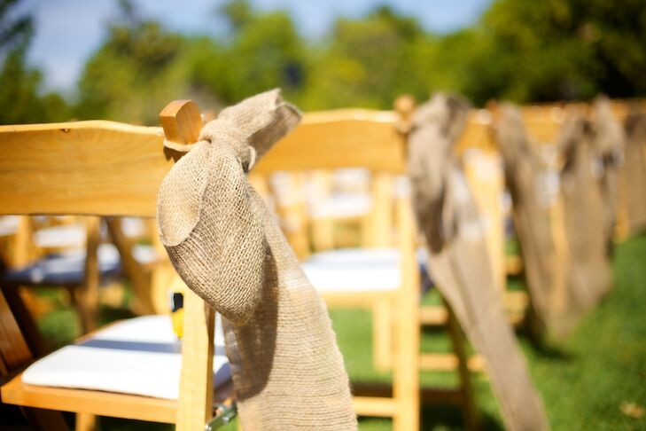 At the outdoor ceremony, burlap aisle decorations were wrapped around wood folding chairs.