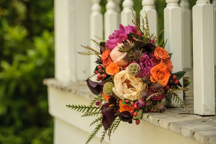 A mix of bright pinks, vibrant orange and moody purple flowers, including roses, calla lilies and peonies, were accented by wispy ferns and scabiosa pods for a romantic, rustic look.