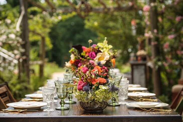 The long wooden reception table was style by Simply Styled with vintage place settings, elegant colored glasses and vibrant floral arrangements by Chelish Moore Flowers that added a pop of color to the rustic setting.