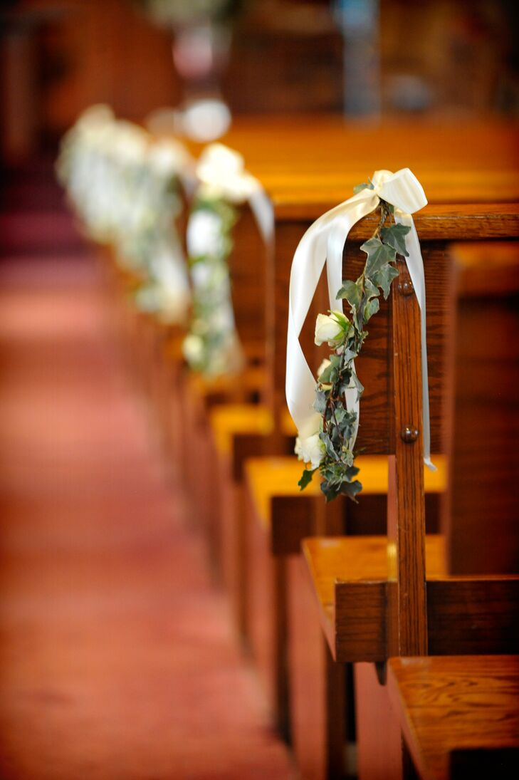 The pews along the ceremony aisle were decorated with ivy and white roses tied with ivory ribbons. This simple touch was all that was needed to decorate the beautiful polished wood pews and warm wood-paneled church where Kieran and Tom were married.