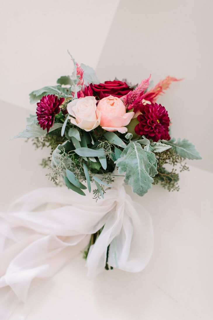 "As a self-proclaimed black thumb, Stefanie gave planner Jackie free rein over the florals. ""I didn't have any special requests, but I sent her pictures from Pinterest of centerpieces and bouquets I liked and trusted her to take care of it—which she did more than I could have expected,"" Stefanie says. For her walk down the aisle, Stefanie carried a dramatic yet dainty bouquet of roses, dahlias, dusty miller, astilbes and seeded eucalyptus wrapped in ethereal chiffon ribbon."