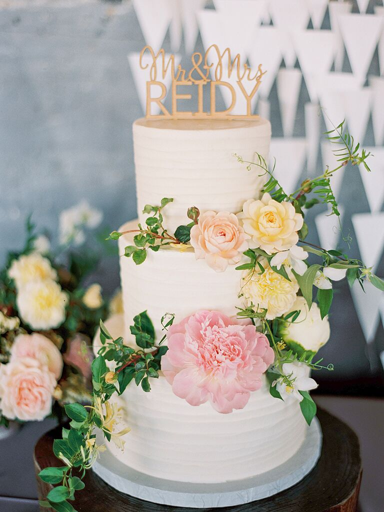 Simple wedding cake with greenery, peonies and ranunculus