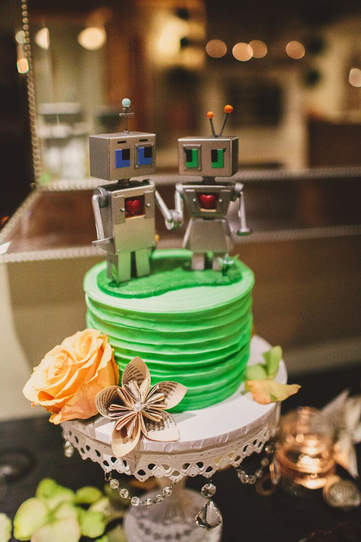 The bright green cake used for cutting had orange blooms decorating the sides of the dessert. The cake had a topper of two love-stricken robots, with the entire dessert displayed on a white elegant stand.
