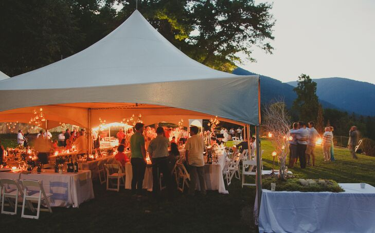 The reception took place outdoors, next to the ceremony site, also overlooking Kootenay Lake in Nelson, British Columbia. The tent roof was lined with white lights and glass terrariums filled with candles.