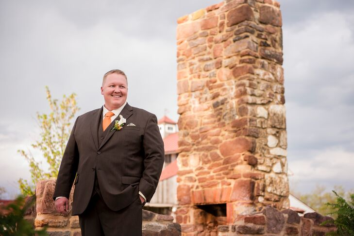 Travis wore a brown suit with an orange tie and calla lily and hypericum boutonniere to his wedding.