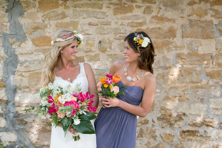 Megan's bridesmaids wore the same strapless slate gray dresses for the bohemian wedding. Megan and Marcus loved how they served as a neutral backdrop for the bold, colorful bouquets. Each lady completed her look with floral statement necklaces.
