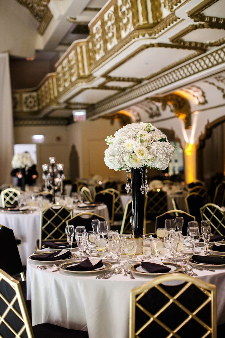 To go with the Crystal Ballroom's gold detailing, Kristen and Alex incorporated bold black-and-white details throughout their reception space—including tall flower arrangements and elegant gold chargers.