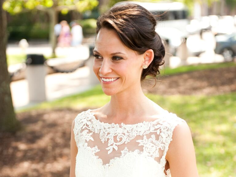 bride with lace bateau wedding dress and low bun