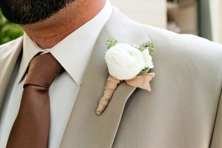 The groom accessorized his light suit with a brown tie and a white ranunculus boutonniere.