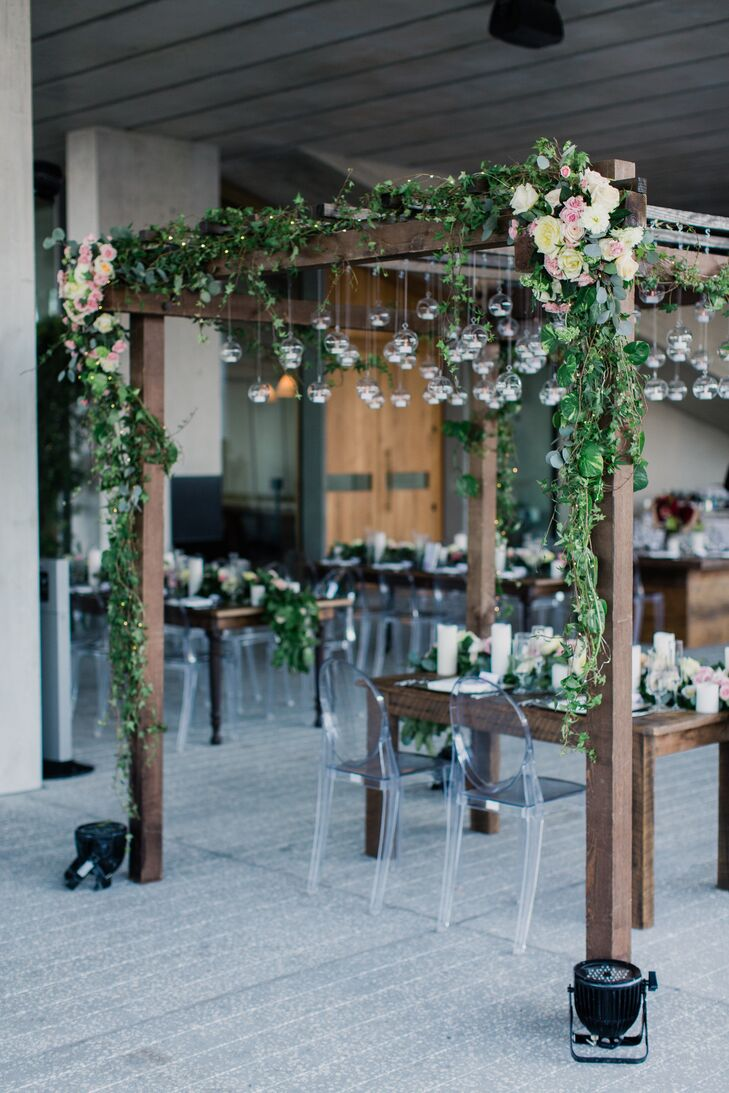 Instead of having a wedding arbor at their ceremony, Kristin and Andrew had a similar construction at their reception. The raw, wooden sweetheart table was surrounded with a matching four-post structure, covered in greenery, roses and hanging glass orbs.