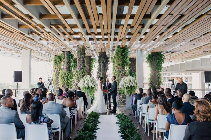 Their ceremony overlooked the Perez Art Museum Miami's hanging greenery for a gorgeous natural view. The Flower Bazaar's florists made sure the added decor blended in perfectly with the aisle lined in greenery and two overflowing accents. Each had a stone urn filled with amaranthus, white delphiniums, baby's breath and even more greenery. Kristin and Andrew loved every part of the design!