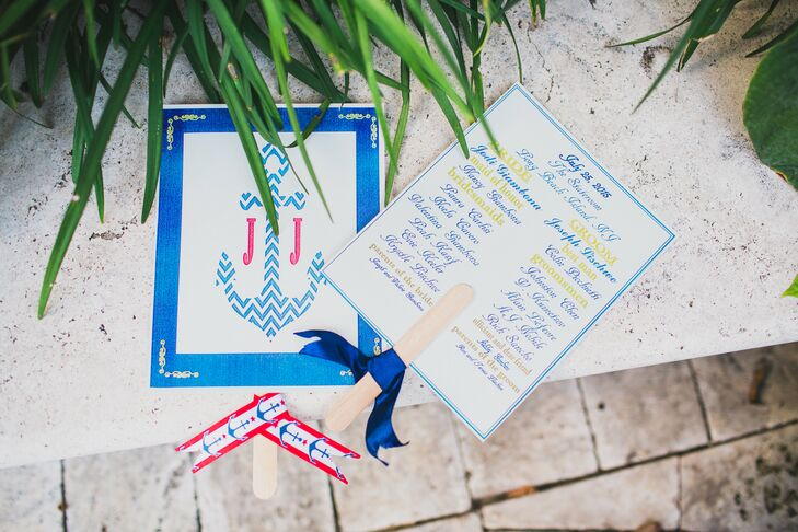 "Jodi and Joe's stationery mixed works by friends and family with items from Minted.com for a custom set. Anchor-clad ceremony fans stood out on every folding chair at the reception at the Stateroom Long Beach Island in Ship Bottom, New Jersey. Wrapped in red and navy ribbon, their full list of wedding party members was printed on the back in yellow or blue script. The front had Jodi and Joe's ""J"" monogram around a chevron blue anchor."