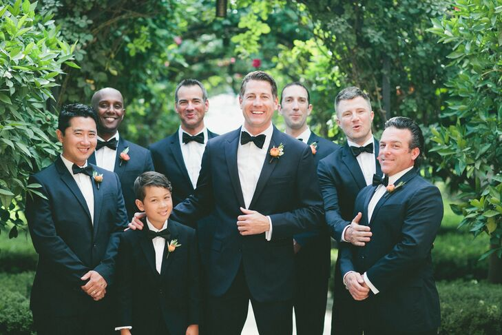 Aron and his groomsmen sported dark navy tuxedos and black bow ties for a modern spin on a classic look that complemented the bridesmaids' dresses.