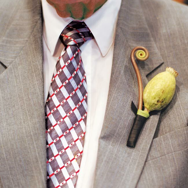 The groomsmen wore poppy pods accented with fiddlehead fern on the lapels of their suits.