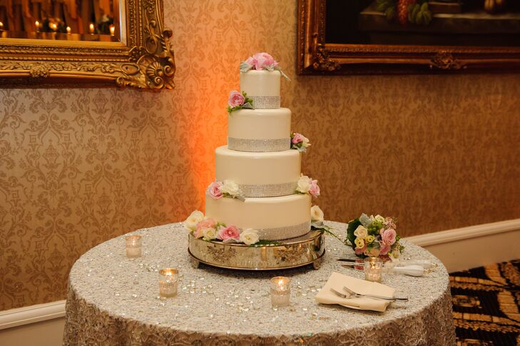 The four-tier white wedding cake was wrapped with silver at the bottom of each tier. The cake was accented with fresh flowers on top and on the sides, and was positioned on a silver cake stand.