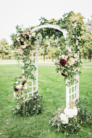 White Wedding Arch Decorated with Greenery, Roses, Hydrangeas, Marigolds and Dahlias