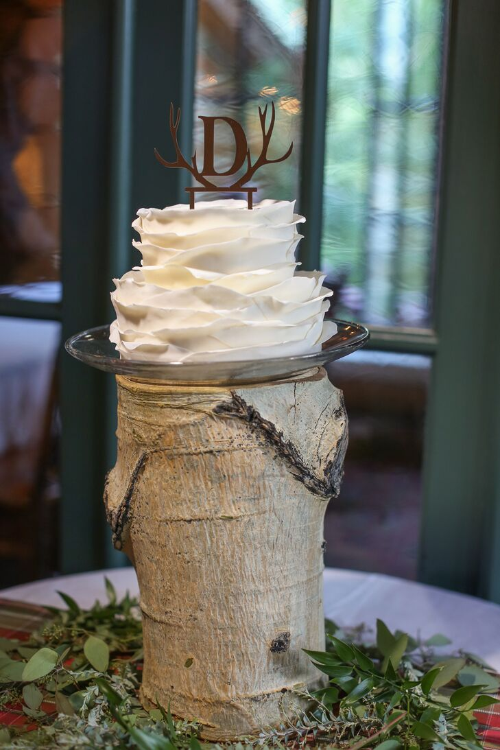 The wedding cake was a personal two-tiered cake just for Stacey and Eric to enjoy. It was decorated with layered white fondant to look like a blooming flower. On top was a signature antler logo that the couple used throughout their decor. The cake was displayed on a high wood trunk that brought the rustic outdoor feel into the cabin.