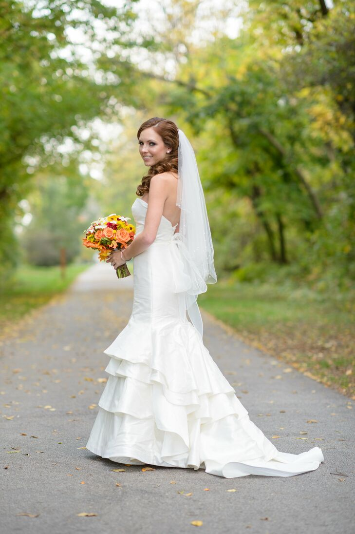 """Elysa wore a mermaid-style wedding dress with a ruffled skirt on her wedding day. She paired it with a fingertip veil. """"I wanted my dress to be unique but simple,"""" she says."""
