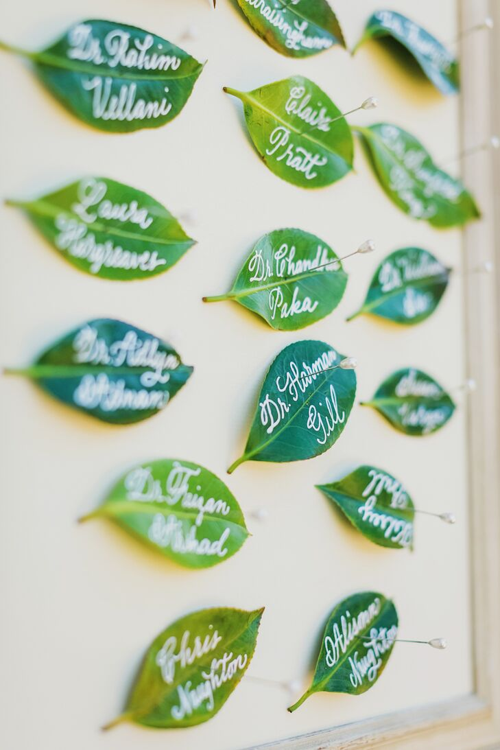 Fitting the event's nature-centric color scheme perfectly, these bright green escort cards (actually, leaves) were penned with guests' names in calligraphy and pinned to a wall organized by table number.
