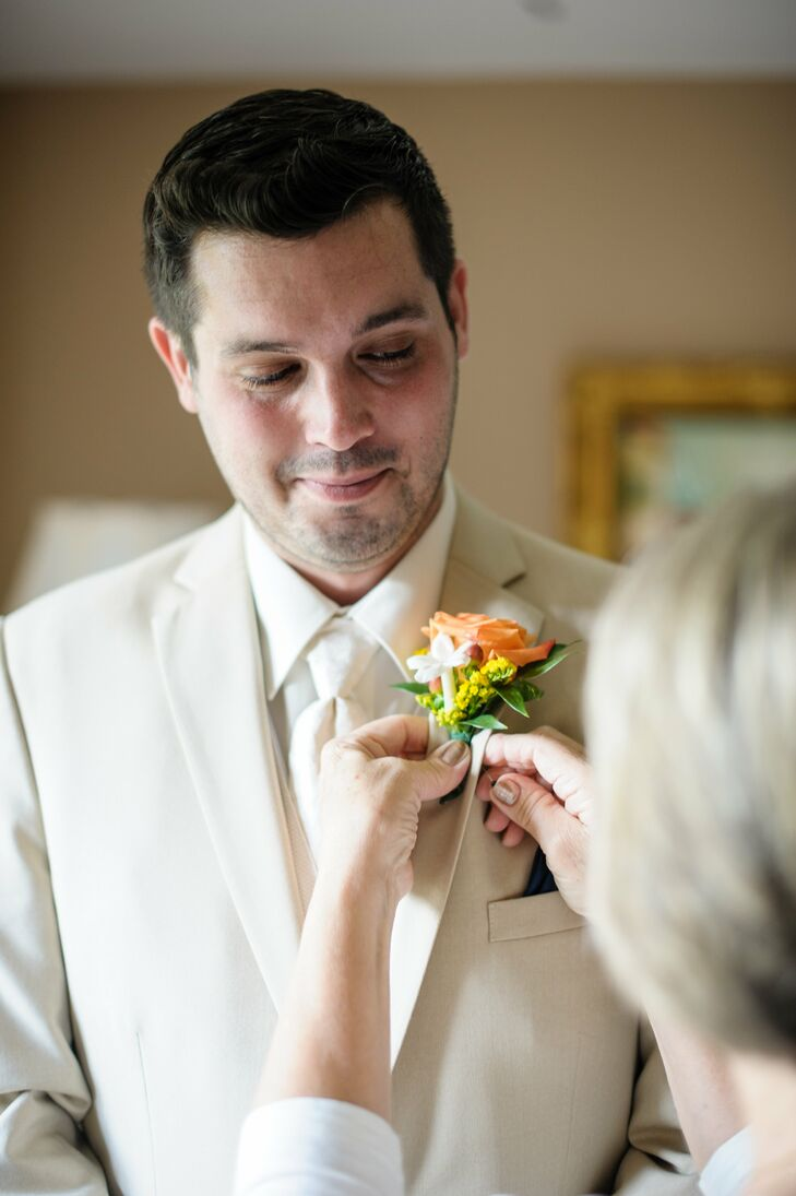 Paul wore a khaki suit and a gray tie on his wedding day. He also wore a peach rose and stephanotis boutonniere to match the fall theme.