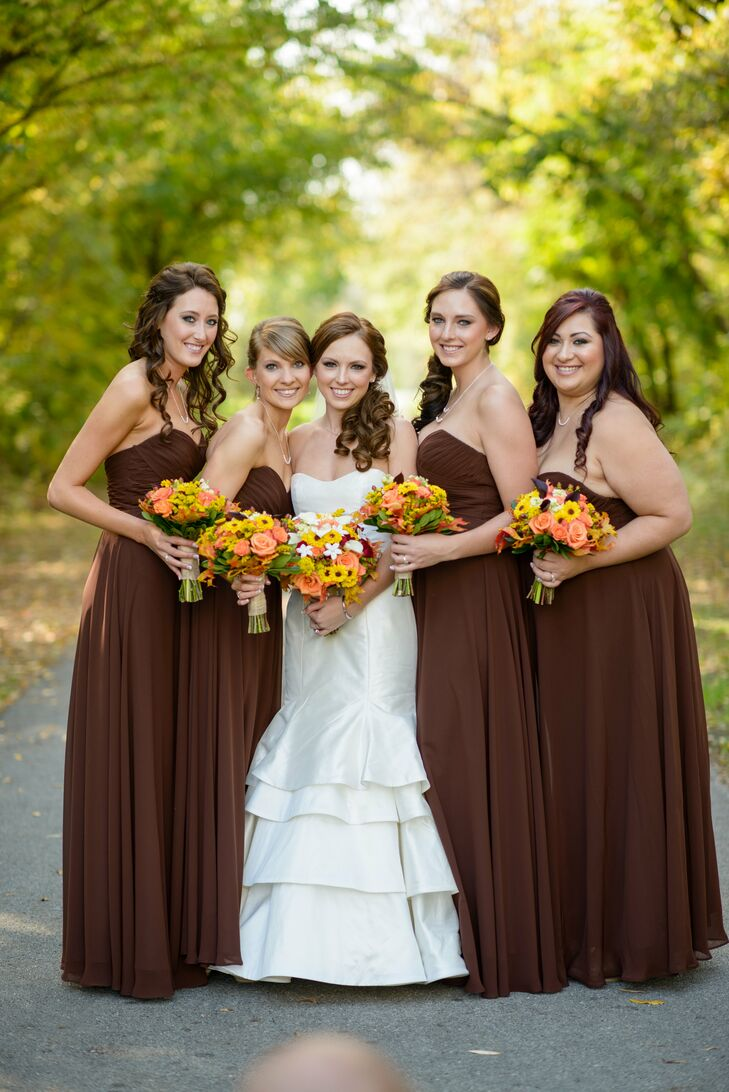 """Elysa's bridesmaids wore strapless, floor length dresses in brown by Jim Hjelm. """"I wanted everyone to be in a neutral fall color that would be flattering on everyone and complement our color scheme,"""" Elysa says."""