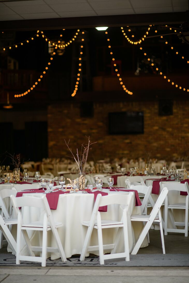 The reception was held in the barn at CD & ME. The white tables were arranged with burgundy linens and the venue was beautifully illuminated by bistro lighting.