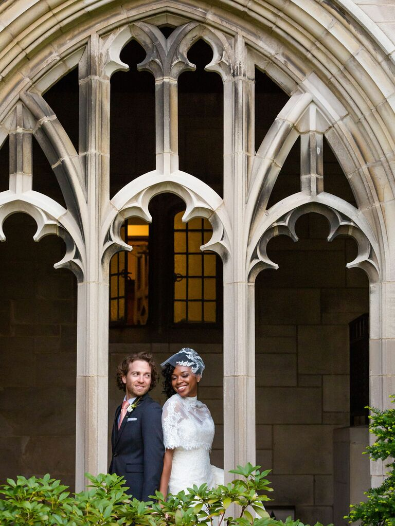 Groom posing with bride wearing vintage lace capelet and blusher veil