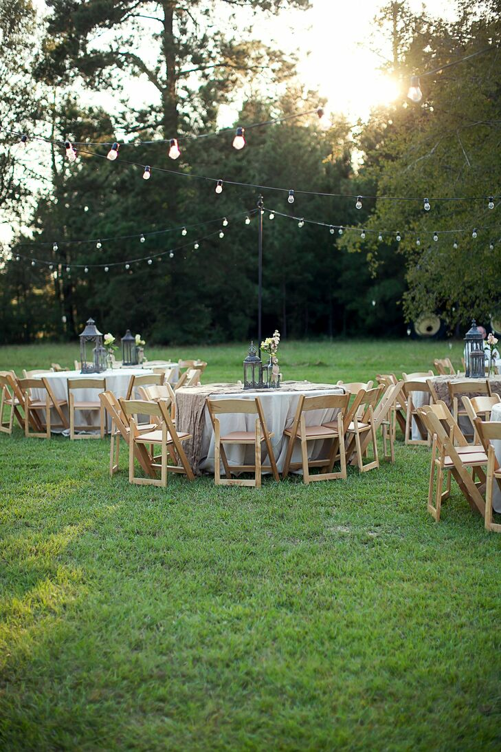 Strings of bistro lights hung over tables draped with natural cloth and decorated with ornate, antiqued pewter lanterns and simple floral arrangements.