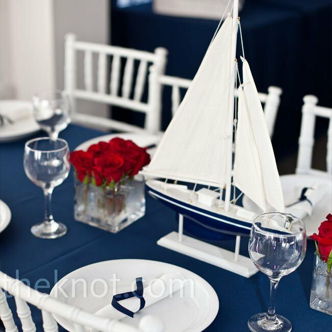 Andrea and Mark found small wooden sailboats and displayed them in the centers of the reception tables. Bluntly cut red roses gave the arrangements a structured geometric shape.