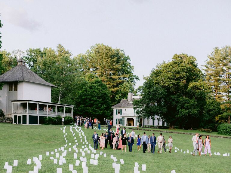 Wedding guests walking through paper lantern pathway at outdoor summer wedding