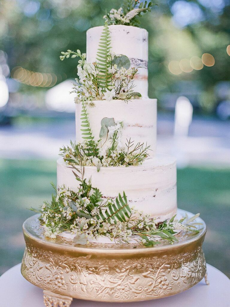 Three-tier rustic wedding cake with fern accents