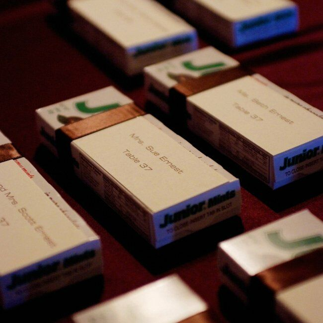 The escort cards doubled as favors. The purple cards were affixed with brown ribbon to boxes of Junior Mints.