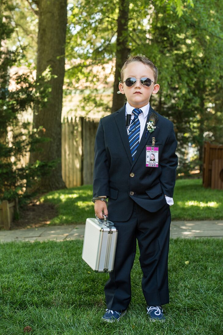"The ring bearer was dressed to look like a secret service agent. He wore aviator glasses, an earpiece and a badge that read ""Ring Security."" Instead of carrying a pillow with the rings, he carried a silver metal briefcase for top-notch security."