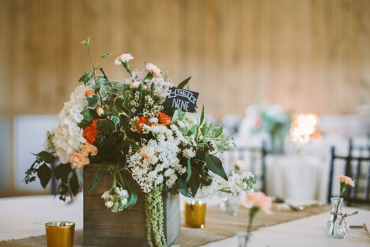 The centerpieces were in wood flower boxes filled with overflowing arrangements of mint, coral and white flowers.