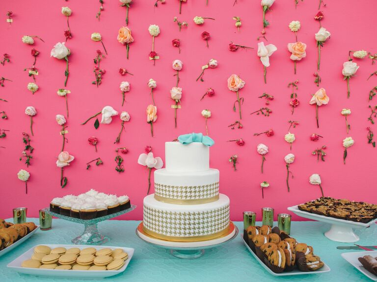 Individual flower stems taped on pink wall around wedding cake and dessert spread