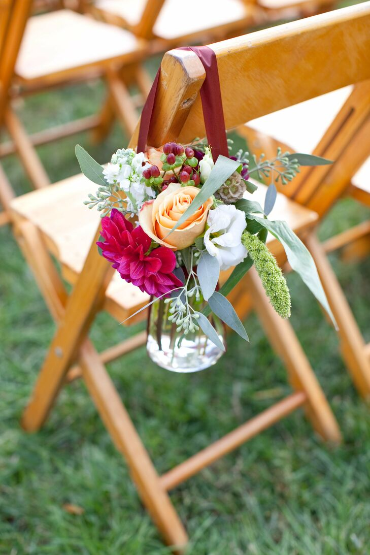 The chairs on the ceremony aisle were decorated with Mason jars hanging from burgundy ribbons. They were filled with flower arrangements of peach roses and red dahlias.