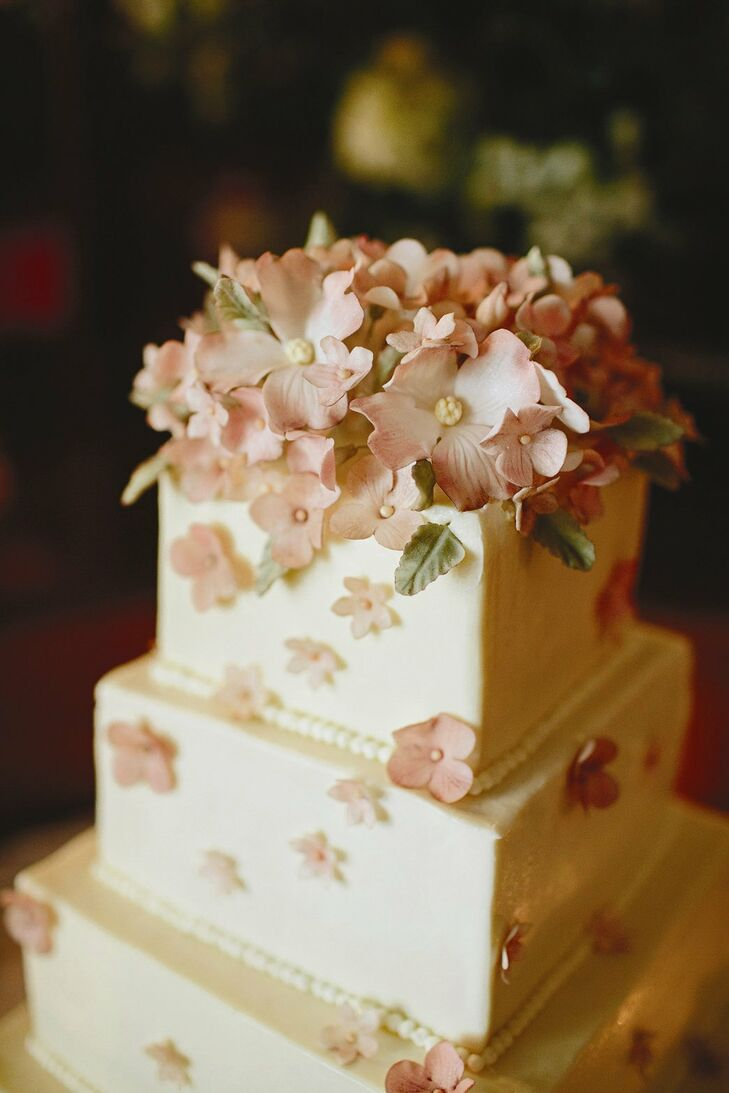 Realistic-looking, edible sugar flowers topped the five-tier wedding cake. Inside, strawberry and almond cake was separated by rich buttercream frosting.