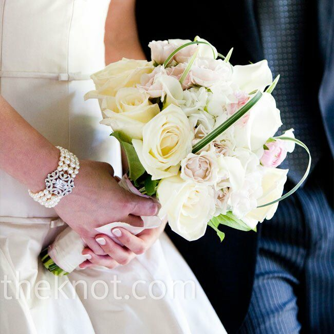 The florist used hydrangea to anchor ivory Virginia roses, white mini callas, soft spray roses, and pale pink ranunculus with a green center. He finished the bouquet with pieces of zebra grass that came from the couple's garden.