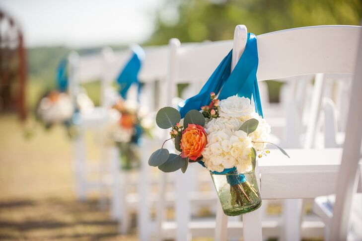The aisles were lined with green glass vases tied with teal ribbons and filled with small arrangements of hydrangea, roses, hypericum berries and dusty miller.